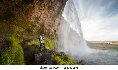 Hiker Woman Looking at the Seljalandsfoss Waterfall  in Iceland