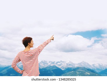 Hiker woman pointing out finger in sky with mountains on background. Travel at Dolomites, Italy, Europe. Summer holiday in South Tyrol. View of Bruneck and Pustertal from the summit of Kronplatz