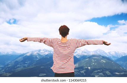 Hiker woman with raised arms up with mountains on the background. Travel at Dolomites, Italy, Europe. Summer holiday in South Tyrol. View of Bruneck and Pustertal from the summit of Kronplatz.