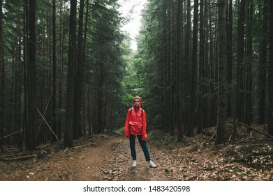 Hiker woman in a red raincoat stands on a trail in the mountains,looks in camera, girl on a mountain hike. Full length photo of tourist in red jacket standing in background of big old coniferous trees
