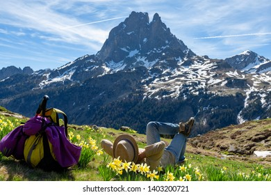 a hiker woman resting and looking the Pic du Midi Ossau in the french Pyrenees mountains