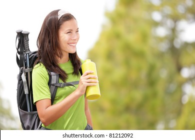 Hiker woman smiling happy drinking water. Female hiking in forest looking to the side. Beautiful multiracial Asian Caucasian female model outdoors in nature.