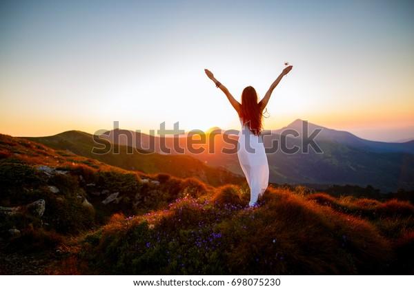 Hiker Frau mit den Händen nach oben zu erreichen. Mädchen heißt eine Sonne willkommen. Konzeptionelles Design. Erfolgreiche Frauen wandern offene Arme auf dem Sonnenaufgang Berggipfel. Mädchen in langen, weißen Kleid in den Bergen.