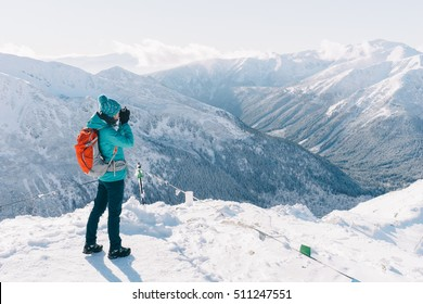 Hiker woman standing and making photos using digital mirrorless camera, admiring winter mountain landscape. Happy tourist woman in winter. High Tatras, 1987 meter above sea level. Poland, Slovakia