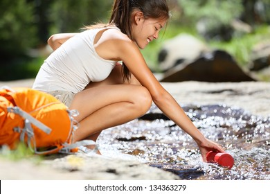 Hiker woman taking water in river in Yosemite National Park after hiking. Happy girl smiling enjoying outdoors summer trekking vacation. Multicultural woman in California, USA.