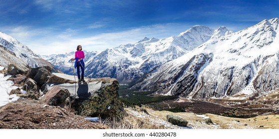 Hiker woman walking on mountain trail with hiking sticks, looking at view in Elbrus region, Caucasus