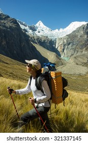 Hiker Woman walking with Trekking Pole and Backpack with an Amazing Background of Alpamayo Mountain - Huaraz, Peru.