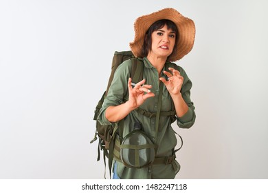 Hiker woman wearing backpack hat and water canteen over isolated white background disgusted expression, displeased and fearful doing disgust face because aversion reaction. With hands raised.