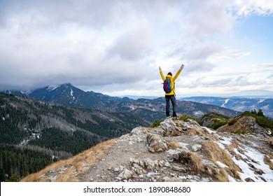 Hiker woman in yellow down jacket on the mountain ridge.