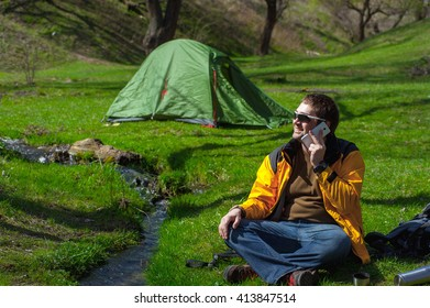 hiker in the woods with a tent relax by the river, and checked his phone