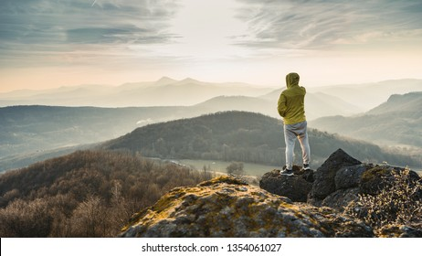 Hiker with yellow jacket watching to Sun at horizon. Beautiful moment the miracle of nature. Colorful mist in valley. Man hike.