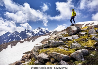 Hiker in yellow shirt with backpack standing on the rock with enjoying the view of snowy mountains at cloudy sky background