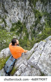 Hiker young man with backpack sitting on a rock and admiring the view on summer season