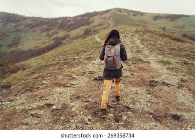 Hiker young woman with backpack climbing on mountain