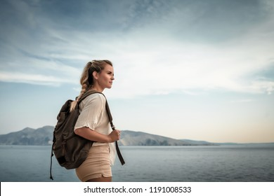 Hiker young woman with backpack on trekking trail looking at sea bay landscape