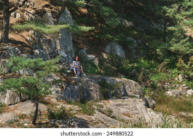 Hiker young woman with backpack resting on stone rock in summer outdoor