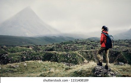 Hiker young woman with backpack walking in front of mountain in fog.