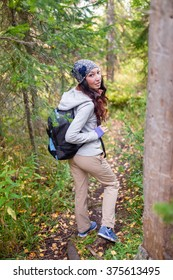 Hiker young woman with backpack walking in autumn forest.