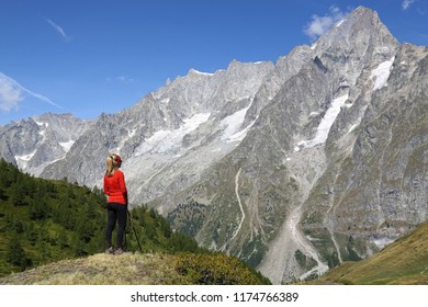 Hiker young woman in Courmayeur. Grand Jorasses and blue sky
