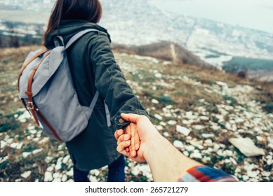 Hiker young woman holding man's hand and leading him on nature outdoor. Couple in love. Focus on hands. Image with instagram filter