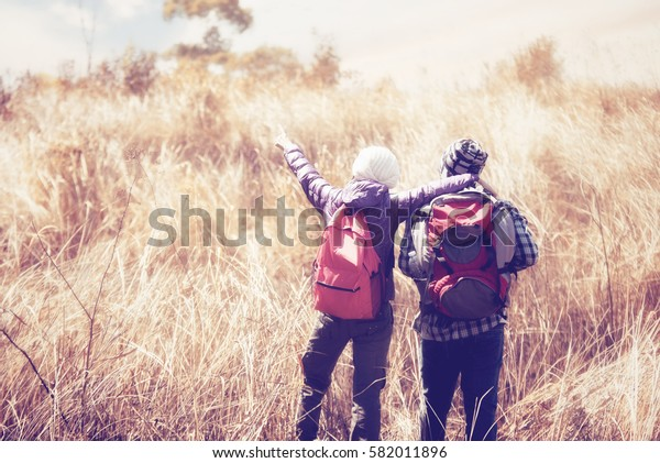 Hiker young woman holding man's hand and leading him on nature outdoor.  Adventure, travel, tourism, hike and people concept - smiling couple with backpacks at Khao Yai National Park, Thailand.