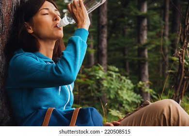 Hiker young woman rests near a tree and drinks water in summer forest