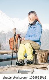 Hiker young woman sitting on wooden bench with thermos and looking at snowy mountains.