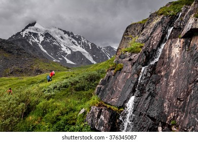 Hikers in Altai mountains near waterfall