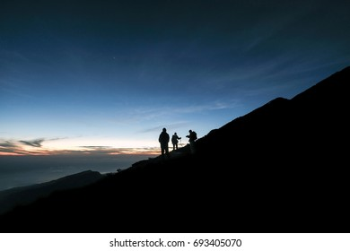 Hikers ascend the mountain slope during blue hour