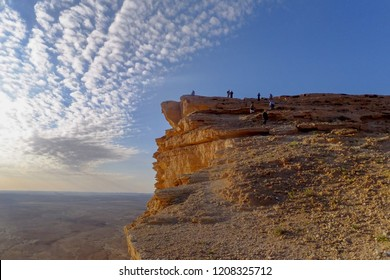 Hikers Atop a Cliff Await the Sunset under a Blue Sky and White Clouds, Edge of the World, Riyadh, Saudi Arabia