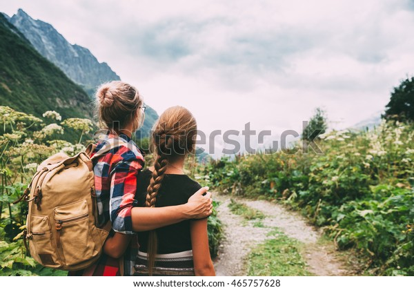 Hikers with backpack looking at mountains, alpine view, mother with child