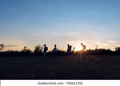 Hikers with backpacks enjoying in mountain hike  the view with sunset sky background