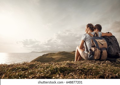 Hikers with backpacks enjoying view of sunset in ocean.Traveling along mountains and coast, freedom and active lifestyle concept