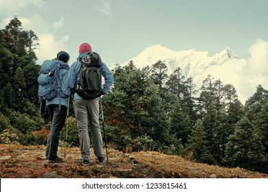 Hikers with Backpacks look on top of mountain, discussing the Rout in high Mountains peak of Himalaya range. Beautiful inspirational landscape, trekking and activity. Travel sport lifestyle concept