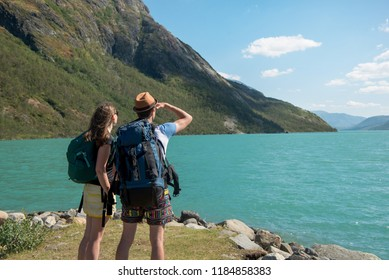 hikers with backpacks looking at Gjende lake in Jotunheimen National Park, Norway