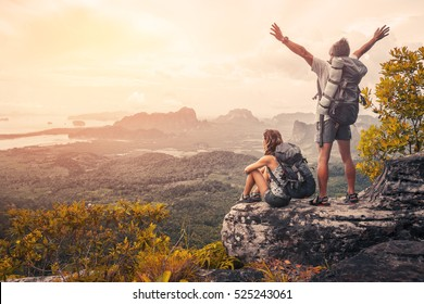 Photo of Hikers with backpacks relaxing on top of a mountain and enjoying the view of valley at sunset