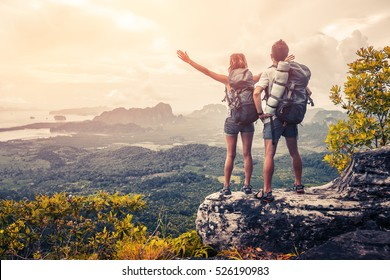 Hikers with backpacks relaxing on top of a mountain and enjoying the view of valley