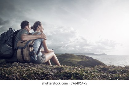 Hikers with backpacks relaxing on top of a hill and enjoying view of sunset in ocean.Island Lombok, Indonesia. Traveling along mountains and coast, freedom and active lifestyle concept