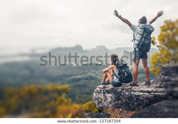 Wanderer mit Rucksäcken, die sich auf einem Berg entspannen und den Blick auf das Tal genießen