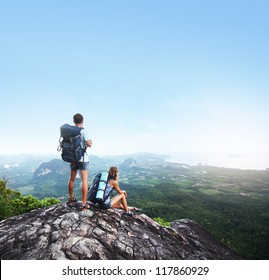 Hikers with backpacks standing on top of a mountain and enjoying a valley view