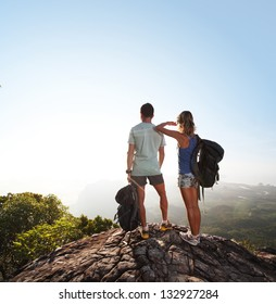 Hikers with backpacks standing on top of a mountain and enjoying sunrise