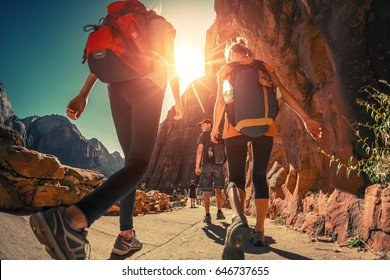 Hikers with backpacks walk on the trail in canyon of Zion National Park, USA