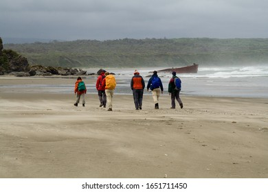 Hikers braving the storm on a West coast beach with the wreck of a Japanese ship. South of the river Chepu, Chiloe Island, Chile.