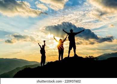 hikers celebrating success on top of a hill in the sunset
