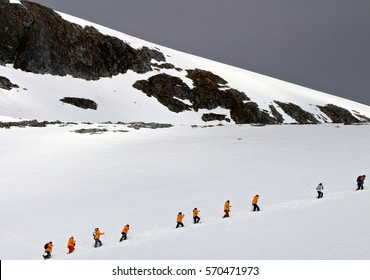Hikers climb a snowy peak on the Antarctic Peninsula.