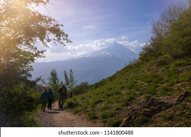 Hikers are climbing the grassy path Damavand mountain is in the background Springtime in Iran.