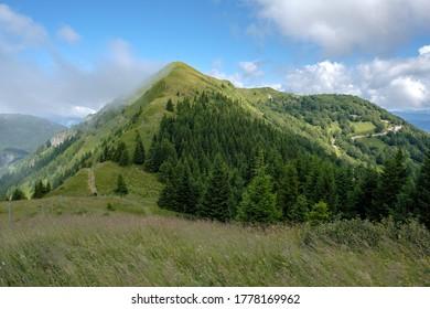 hikers climbing the ridge of the grassy hill while fog/cloud sticks to the left side of the ridge; location Soriska planina, Slovenia