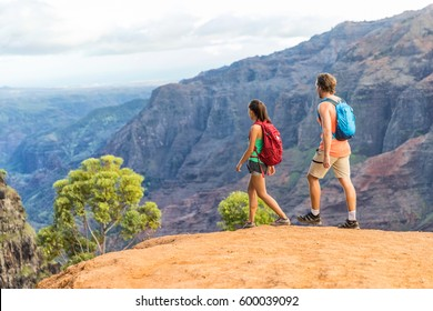 Hikers couple hiking in mountains landscape. Woman and man walking on hike in Waimea Canyon State Park, Kauai, Hawaii, USA. Looking at view happy enjoying healthy outdoor lifestyle.
