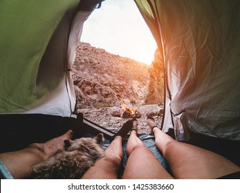 Hikers couple inside tent, camping in rock mountains with their dog - Sporty people relaxing after a trekking day next fire at sunset - Travel ,love and living in nature concept - Focus on feet