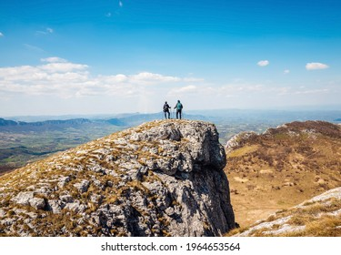Hikers couple standing on mountain cliff lookig to view on valley on Borski Stol mountain in Serbia. Hikers on mountain cliff - Shutterstock ID 1964653564